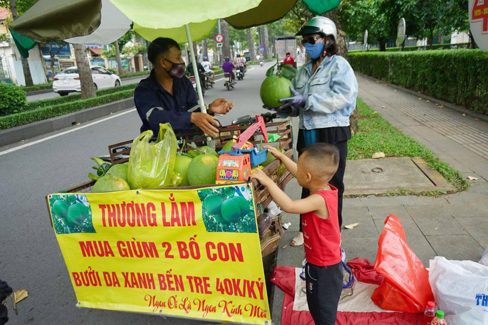 Trăm người mua ủng hộ 2 bố con bán hoa quả với tấm biển độc đáo ở vỉa hè SG - 1